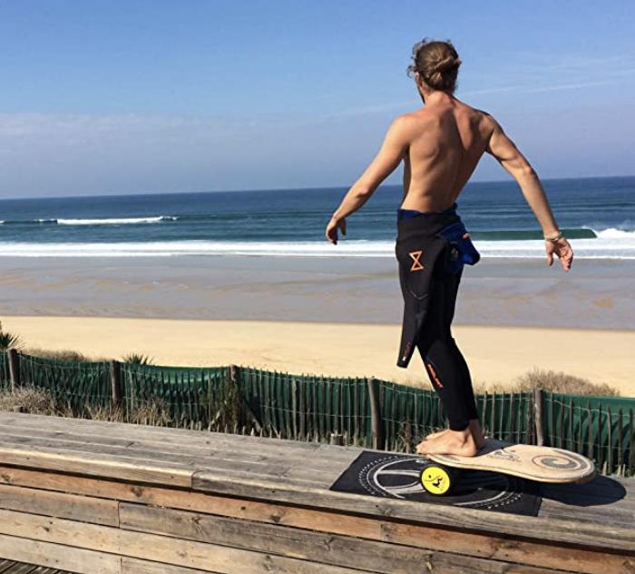 Rollerbone plateau rouleau sur un tapis devant la plage avec un sportif et sa combinaison